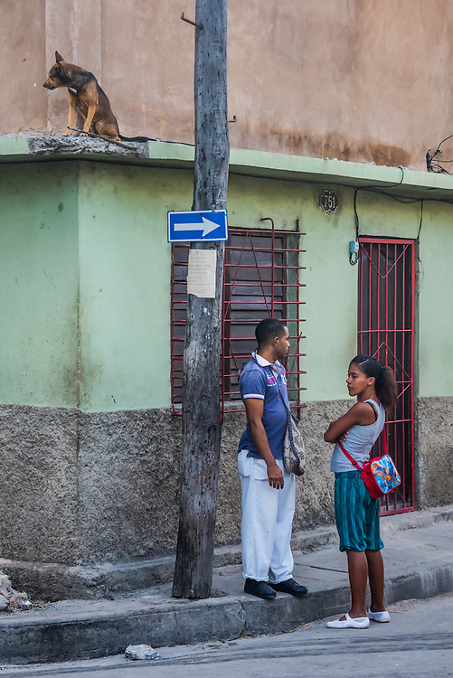 A couple waiting on the street in Santiago, Cuba. Each looks in the opposite direction, seemingly oblivious to the dog sitting on a ledge above them, looking around the corner.