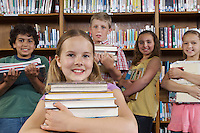 School children holding books in library, portrait
