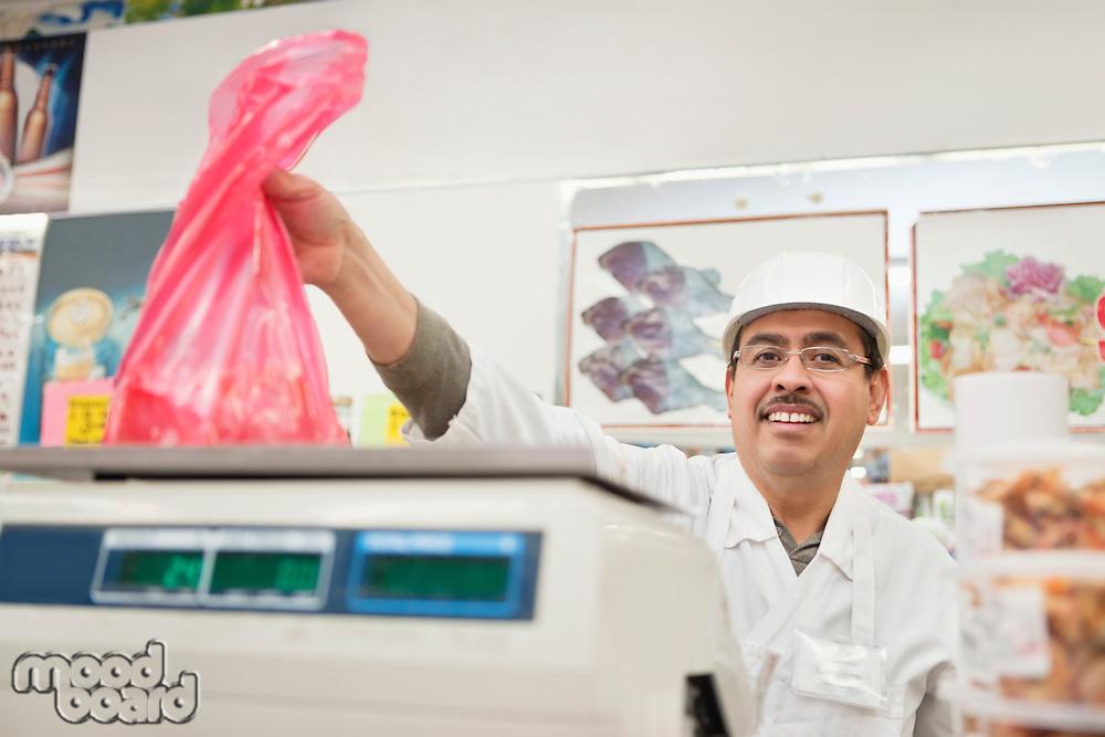 Portrait of butcher giving away meat in plastic bag