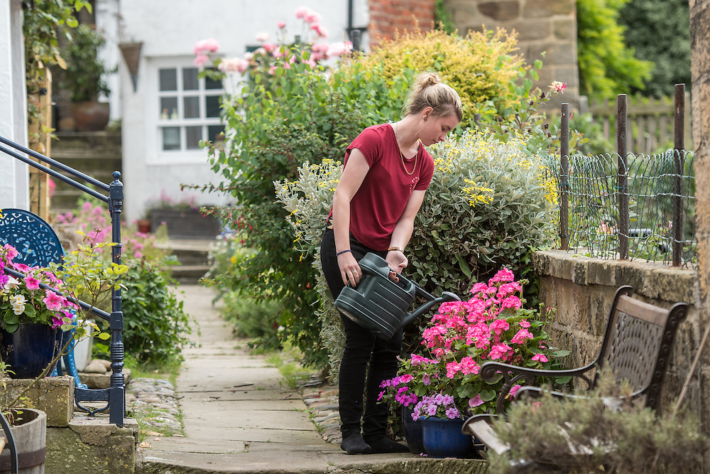 UK, England, Yorkshire - A young woman watering her flowers in a small fishing village called Robin Hood's Bay, located on the coast of North Yorkshire, England.