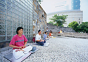 People meditating in City Hall Plaza adjacent to Taipei 101.