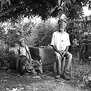 """Ras Beery and his son Junior.<br /> <br /> Ras Beery is a senior member of the Twelve Tribes of Israel Church in Shashamane. Originally from Jamaica, he repatriated 10 years ago. I first met him in 2014 during my last visit.<br /> <br /> He is a gently spoken, articulate man with great knowledge and perspective about the Rastafarian community in Shashamane. His views are direct and offer refreshing realities of Rastafarian life in Zion.<br /> <br /> The Twelve Tribes are generally considered the most moderate of the three Mansions of Rastafarians. It was founded in 1968 by Dr. Vernon """"Prophet Gad """". Members are free to worship in a church of their choice or even at home.<br /> <br /> Members consider themselves the direct descendants of the 12 Sons of Jacob. The 12 Sons are divided into 12 Houses which are determined by your birth month (I am born in July so am considered Judah).<br /> <br /> They also teach to read the bible at least once every day."""