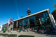 A picture of bicycles lining the Zoo building in Copenhagen on a clear and sunny day.