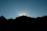 The sun rises on the winter solstice over the peaks of the Andes mountains surrounding and shielding Machu Picchu.