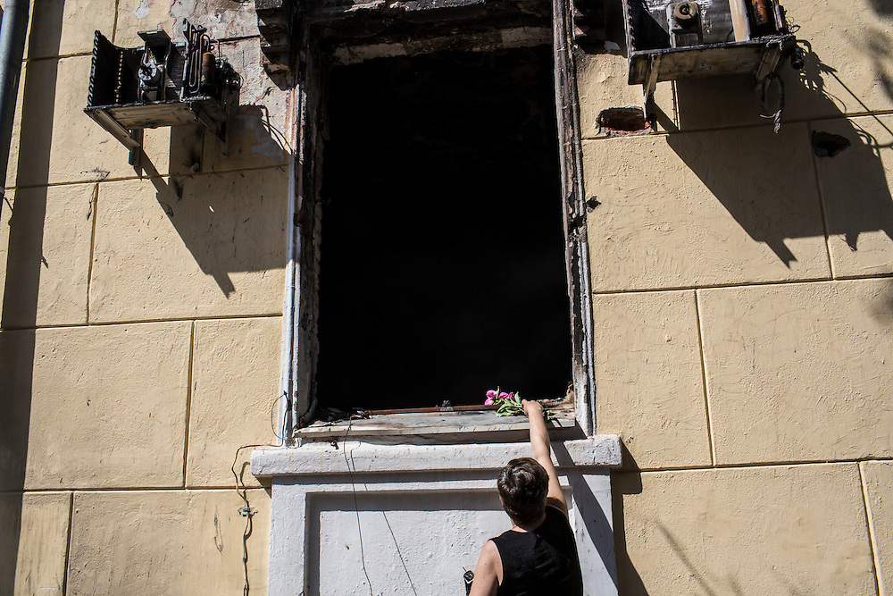 MARIUPOL, UKRAINE - MAY 18: A woman places flowers on a windowsill at a police station which was earlier destroyed in a violent clash, resulting in seven deaths, on May 18, 2014 in Mariupol, Ukraine. A week before presidential elections are scheduled, questions remain whether the eastern regions of Donetsk and Luhansk are stable enough to administer the vote. (Photo by Brendan Hoffman/Getty Images) *** Local Caption ***