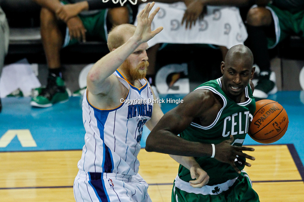 December 28, 2011; New Orleans, LA, USA; Boston Celtics power forward Kevin Garnett (5) drives past New Orleans Hornets center Chris Kaman (35) during the second quarter of a game at the New Orleans Arena. The Hornets defeated the Celtics 97-78.   Mandatory Credit: Derick E. Hingle-US PRESSWIRE