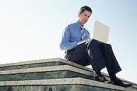 Young business man sitting on marble platform using laptop.