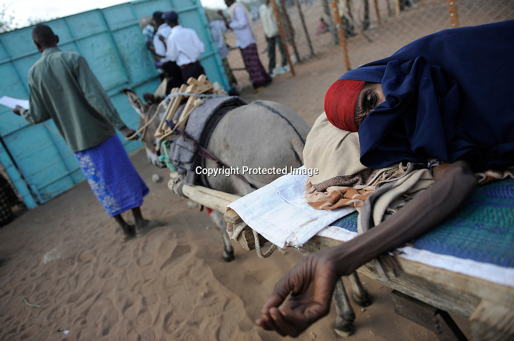 Somali refugees in Dadaab seek medical attention for a family member near the registration centers for the massive camps.
