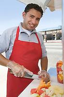 Portrait of male street vendor chopping fruit