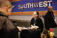 Southwest Airlines employee Brittany Eberson takes baggage for a passenger at Philadelphia International Airport December 29, 2005 in Philadelphia, Pennsylvania. (Photo by William Thomas Cain)