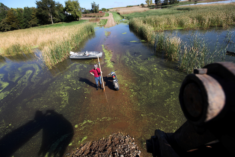 Mark DeSchepper stands in his driveway flooded by agricultural drainage while an excavator carves out a bed for a new culvert in rural Humboldt, S.D., Sat., Sept. 26, 2010. Parts of the 160 acres DeSchepper owns is under nine feet of water.