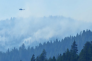 A skycrane helicopter flies over the Tepee Mountain Fire in the Purcell Mountains after making a water drop during the 2015 fire season. Kootenai National forest, northwest Montana.