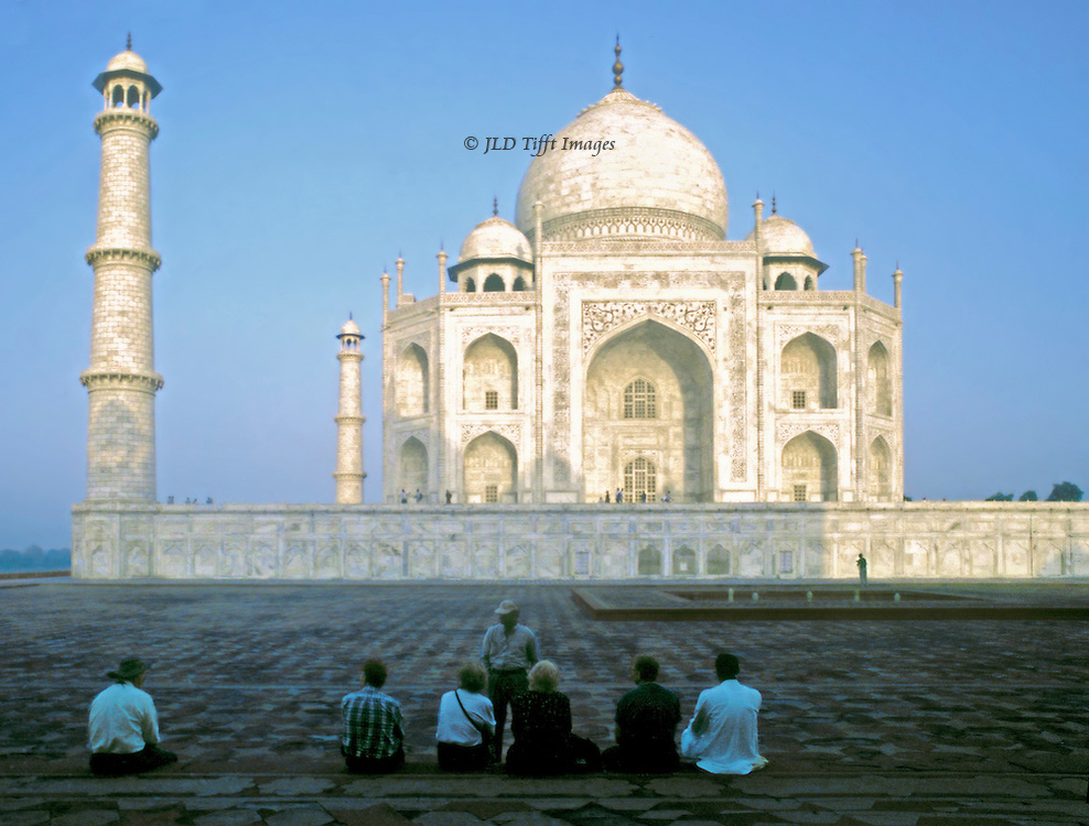 Taj Mahal from the east at sunrise, with a row of 7 visitors seated in the foreground shadow. One minaret visible at the left..