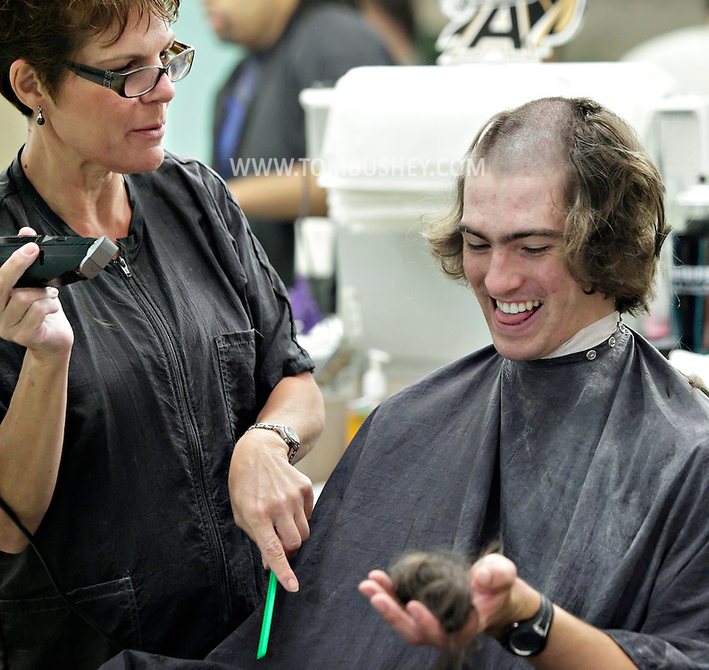 "Renee Daniele, at left, gives a new cadet a handfull of his hair while giving him his ""free haircut"" during R-Day at the U.S. Military Academy at West Point on Monday, July 2, 2012. About 1,150 cadet candidates reported to West Point for Reception Day for the Class of 2016."