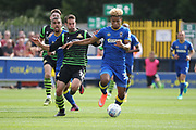 AFC Wimbledon striker Lyle Taylor (33) dribbling and battles for possession with Doncaster Rovers midfielder Matty Blair (17) during the EFL Sky Bet League 1 match between AFC Wimbledon and Doncaster Rovers at the Cherry Red Records Stadium, Kingston, England on 26 August 2017. Photo by Matthew Redman.