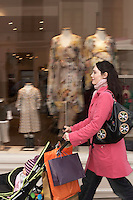 Mother pushing stroller past clothes shop on street