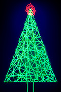 A Christmas tree display made of glowing string, topped with a radiant star.Black light