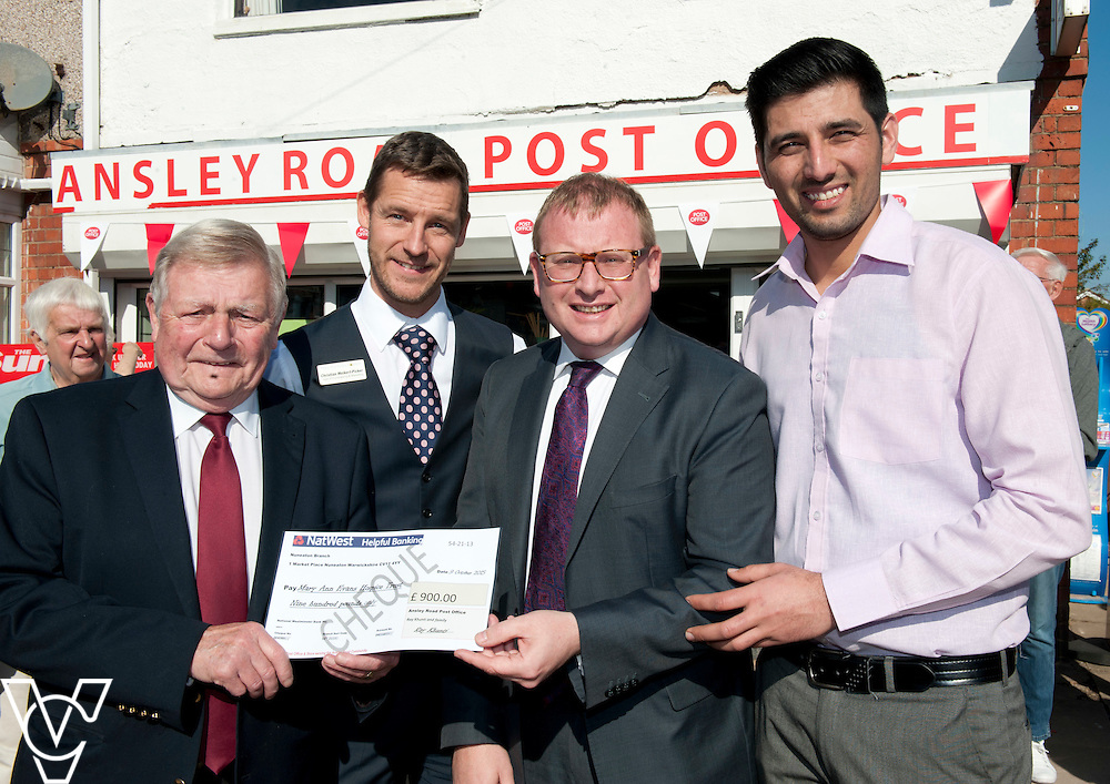A cheque for &pound;900 was presented to the Mary Ann Evans Hospice Trust at the opening of Ansley Road Post Office, Nuneaton.  Pictured, from left, Mary Ann Evans Hospice Trust president Councillor Bill Olner, Mary Ann Evans Hospice Trust head of fundraising and marketing Christian Weikert-Picher, Marcus Jones MP and postmaster Ray Khunti.<br /> <br /> Marcus Jones MP has cut the ribbon to officially open the modernised Ansley Road Post Office, Nuneaton.<br /> <br /> Date: October 9, 2015