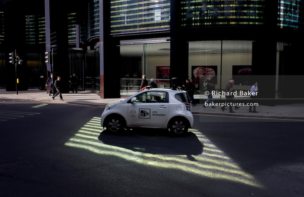 A City of London CCTV enforcement car drives through green reflected light shining from an office building.