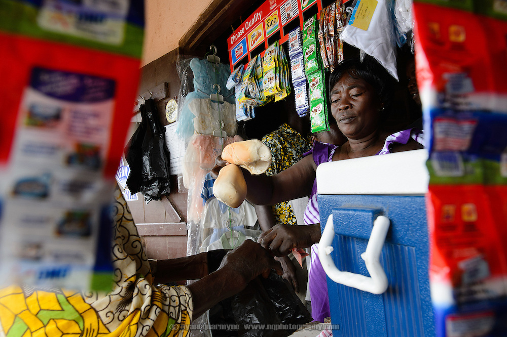 Through her participation in a 'Banking on Change' Village Savings and Loan Association (VSLA), Vincentia Dei-Zanga was able to purchase a motorcycle which she hires out as an 'okada', or motorcycle taxi. She is pictured serving a customer at her shop in Asiekpe in the Volta Region of Ghana on 12 September 2012.