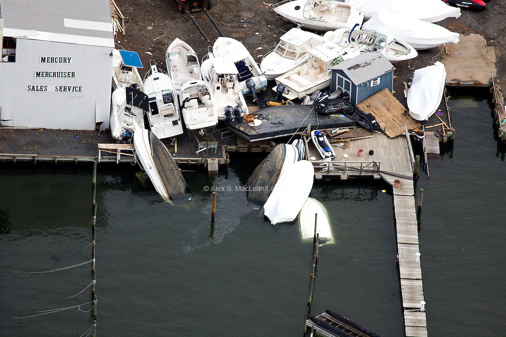 Beached and sunken boats that were left in the water before Hurricane Sandy. (Note the water pollution from fuel spill.)