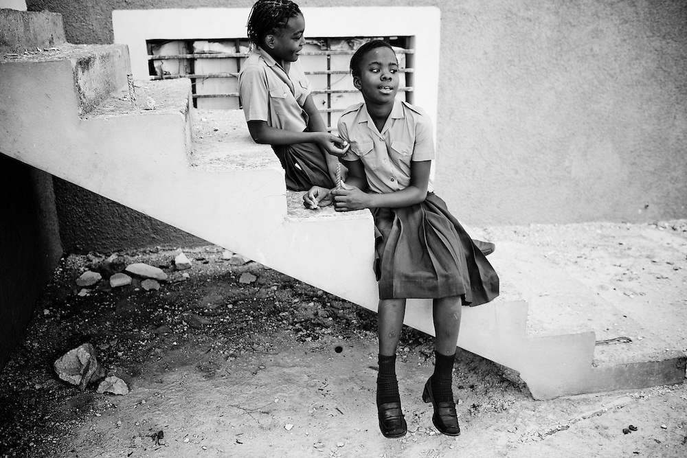 Two girls sit outside during Sunday church services at Eglise Baptiste Bellevue Salem MEBSH church in Port-au-Prince, Haiti.