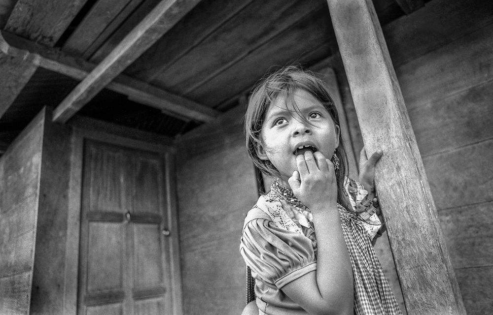 "A young girl in the village of Benito Juarez, anticipates the arrival of ""outsiders"" - medical personnel.  Chiapas, Mexico."