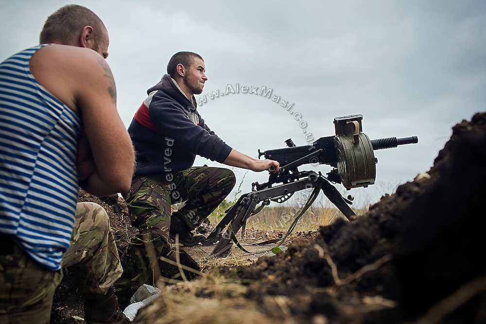 Soldiers are shooting with an automatic mini-grenade launcher towards the position of four men, seen trying to remove a line of anti-tank mines positioned by the Ukrainians on the frontline of Hranitne, near Mariupol, southeast Ukraine.