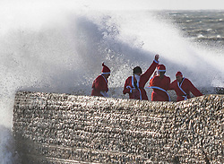 © Licensed to London News Pictures. 14/12/2019. Brighton, UK. A group of people dressed as Santa get drenched by a wave that hits the pontoon alongside Brighton Palace Pier. Photo credit: Hugo Michiels/LNP