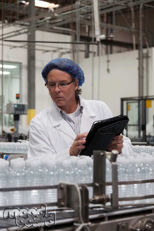 Man at bottling plant inspecting bottled water on conveyor
