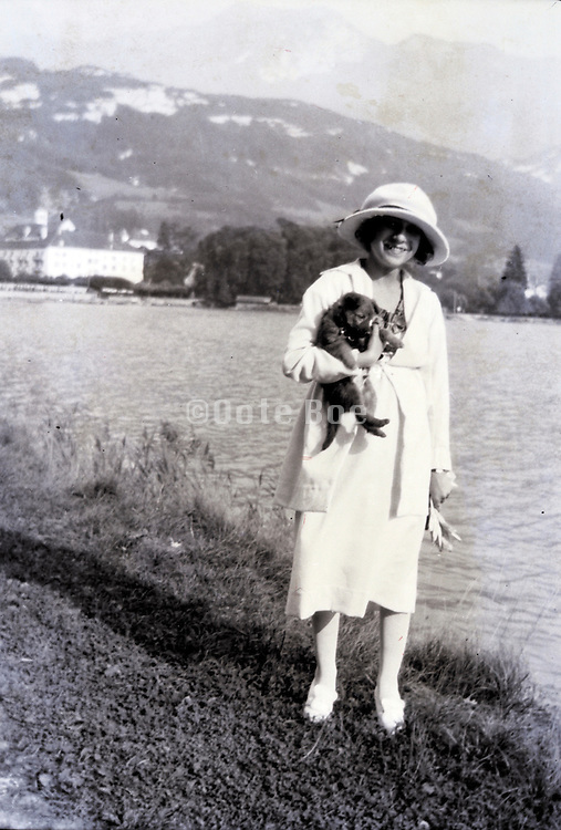 woman with pet dog by lake 1920s