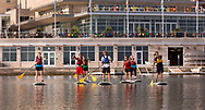 Students stand-up paddle board on Lake Mendota in front of the Terrace at Memorial Union in 2014.