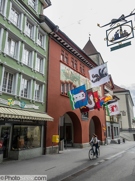 Bicyclist. In Appenzell village, the Rathaus (built 1560-83) houses the city hall, Appenzell Museum, tourist office and library, on Hauptgasse (Main Street), in Switzerland, Europe. The Rathaus facade mural was painted by August Schmid from Diessenhofen (1928). Appenzell Museum shows a cross section of the Swiss Canton's history and culture (1400s flags and banners, embroidery, folk art, and even historic torture instruments). Appenzell village is in Appenzell Innerrhoden, Switzerland's most traditional and smallest-population canton (second smallest by area).