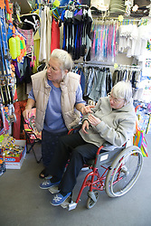 Wheelchair user with Multiple Sclerosis and her carer shopping whilst on a day trip to Skegness organised by Nottingham Disabled Friendship Club,