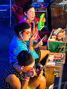 "18 AUGUST 2014 - BANGKOK, THAILAND: Members of the Lehigh Leng Kaitoung Opera troupe put on their makeup before a performance at Chaomae Thapthim Shrine, a small Chinese shrine in a working class neighborhood of Bangkok. The performance was for Ghost Month. Chinese opera was once very popular in Thailand, where it is called ""Ngiew."" It is usually performed in the Teochew language. Millions of Chinese emigrated to Thailand (then Siam) in the 18th and 19th centuries and brought their culture with them. Recently the popularity of ngiew has faded as people turn to performances of opera on DVD or movies. There are still as many 30 Chinese opera troupes left in Bangkok and its environs. They are especially busy during Chinese New Year and Chinese holiday when they travel from Chinese temple to Chinese temple performing on stages they put up in streets near the temple, sometimes sleeping on hammocks they sling under their stage. Most of the Chinese operas from Bangkok travel to Malaysia for Ghost Month, leaving just a few to perform in Bangkok.      PHOTO BY JACK KURTZ"