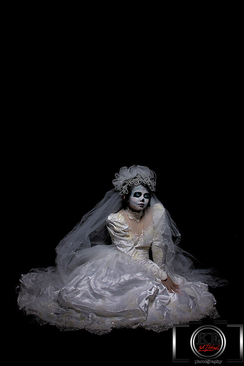 A corpse bride in a beautiful bridal dress with eerie, piercing eyes, sitting there, just staring at you.