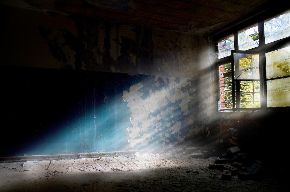 Sunlight shining through an old broken window