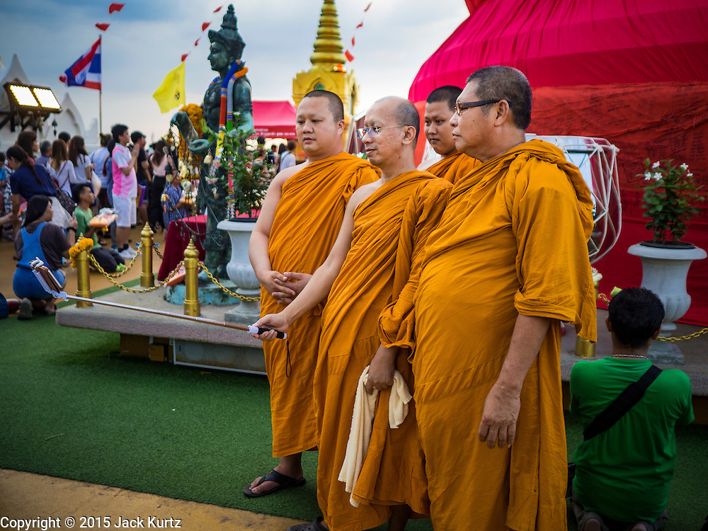 """21 NOVEMBER 2015 - BANGKOK, THAILAND: Buddhist monks pose for a """"selfie"""" at the Wat Saket temple fair. Wat Saket is on a man-made hill in the historic section of Bangkok. The temple has golden spire that is 260 feet high which was the highest point in Bangkok for more than 100 years. The temple construction began in the 1800s in the reign of King Rama III and was completed in the reign of King Rama IV. The annual temple fair is held on the 12th lunar month, for nine days around the November full moon. During the fair a red cloth (reminiscent of a monk's robe) is placed around the Golden Mount while the temple grounds hosts Thai traditional theatre, food stalls and traditional shows.     PHOTO BY JACK KURTZ"""