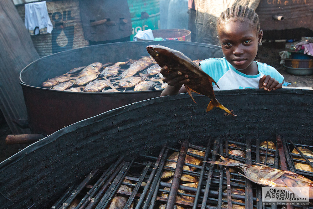 A girl picks up a large smoked fish in the West Point slum of Monrovia, Montserrado county, Liberia on Monday April 2, 2012.