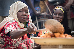 "30 May 2019, Mokolo, Cameroon: Today is market day, and refugees and host communities alike gather to sell and buy goods in Minawao. Here, Falta Mustafa makes ""Kosi"", or 'bean cake' which she sells at the market. The Minawao camp for Nigerian refugees, located in the Far North region of Cameroon, hosts some 58,000 refugees from North East Nigeria. The refugees are supported by the Lutheran World Federation, together with a range of partners."