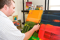 artist working on an abstract painting with a knife or trowel