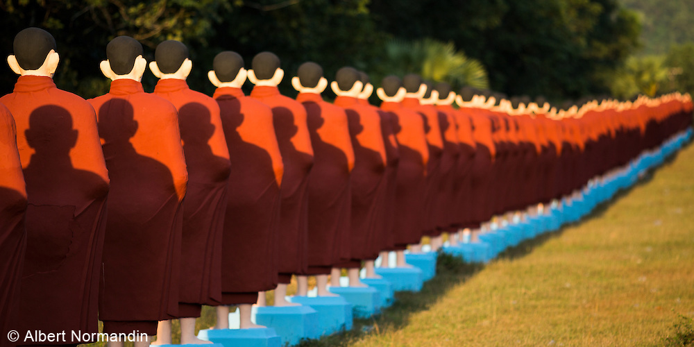 Long line of standing Monk statues at entrance of Win Sein Taw Ya reclining Buddha statue, Mudon,  Mawlamyine