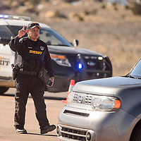 McKinley County Sheriff's deputy Jonathan Todachine directs traffic away from the intersection of Rico Street and Rollie Road where the area was blocked following a bomb threat at Gallup High School Wednesday.