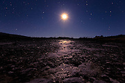 A barren landscape and the moon, at Butcher's Dam, New Zealand