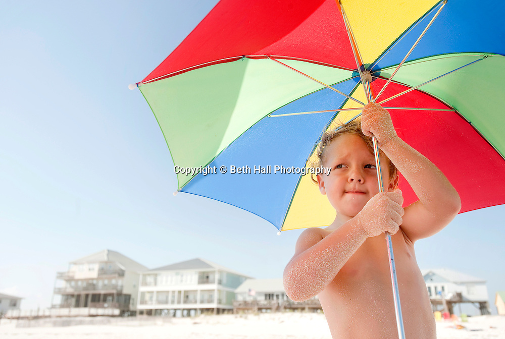 A 3 year old boy is shaded from the sun under an umbrella while playing at the beach.