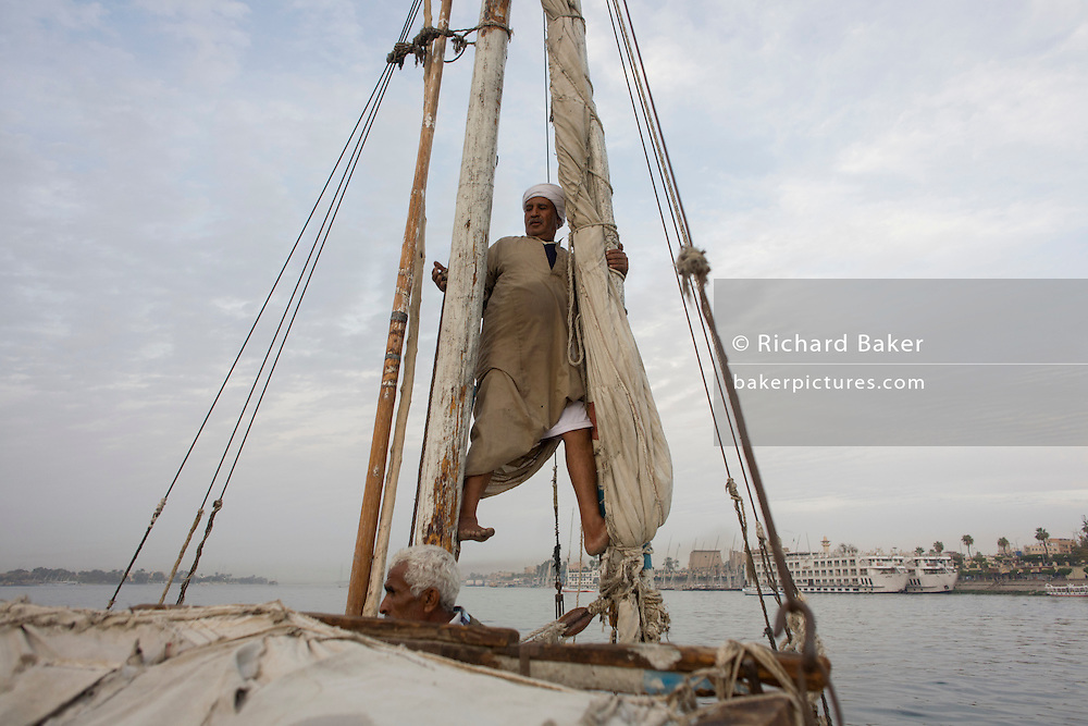 A crewman of a felucca prepares the sail during a journey on the River Nile at Luxor, Nile Valley, Egypt. Feluccas are ancient Egyptian sail boats which were used in ancient times as a primary mode of transport and are the only type of boat that is still used extensively in the country.