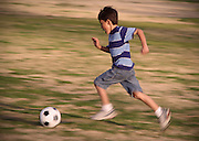 Boy runs after soccer ball - with motion blur