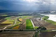 Nederland, Noord-Brabant, Werkendam, 23-10-2013; Ruimte voor de Rivier project Ontpoldering Noordwaard. Het deel rechtsboven is reeds ontpolderd, onder het gedeelte in ontwikkeling waar boerderijen en particuliere huizen op nieuw opgeworpen terpen gebouwd worden. Midden in beeld een nieuwe dijk, hierlangs zal het water stromen, vanaf rivier de Nieuwe Merwede  de bestaande dijk krijgt een instroom opening.<br /> Delen van de polder (links) wordt ontpolderd en de dijken worden verlegd en/of verlaagd waardoor bij hoogwater het rivierwater ook door de polder sneller weg kan stromen richting zee. Gevolg van de ingrepen is ook dat de waterstand verder stroomopwaarts zal dalen.<br /> National Project Ruimte voor de Rivier (Room for the River) By lowering and / or moving the dike of the Noordwaard polder the area will become subject to controlled inundation and function as a dedicated water detention district. Houses and farmhouses will be constructed on new dwelling mounds. <br /> luchtfoto (toeslag op standard tarieven);<br /> aerial photo (additional fee required);<br /> copyright foto/photo Siebe Swart