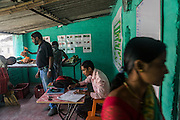 Jeevika Field Associate Raju Kumar (in pink shirt) keeps records and issues receipts to producer group farmers selling vegetables to the collection centre in Machahi village, Muzaffarpur, Bihar, India on October 27th, 2016. Non-profit organisation Technoserve works with women vegetable farmers in Muzaffarpur, providing technical support in forward linkage, streamlining their business models and linking them directly to an international market through Electronic Trading Platforms. Photograph by Suzanne Lee for Technoserve