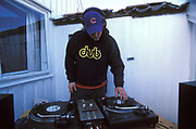 DJ wearing sweatshirt with the inscription 'dub' playing records outdoors.